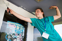 """Margaux Bereuter rolls paint outside of an entryway during """"Circle the City with Service,"""" the Kiwanis Circle K International's 2015 Large Scale Service Project, on Wednesday, June 24, 2015, at the Friendship Westside Center for Excellence in Indianapolis. (Photo by James Brosher)"""