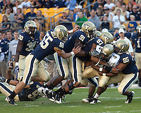 The Pitt defense led by Max Gruder (55), Greg Romeus (91), Jabaal Sheard (97) and Mick Williams (95) gang tackle Navy quarterback Ricky Dobbs. The Pittsburgh Panthers defeated the Navy Midshipmen 27-14 at Heinz Field, Pittsburgh, PA.