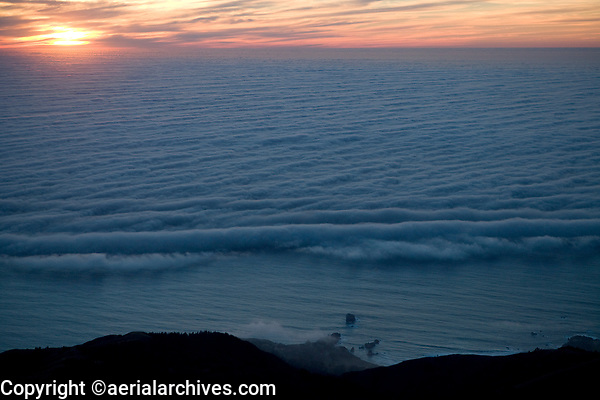 aerial photograph of a layer of fog over the Pacific ocean moving toward the coast at Big Sur, Monterey County, California