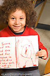 Education Preschool 4-5 year olds art activity proud boy showing his drawing recognizable human figure vertical