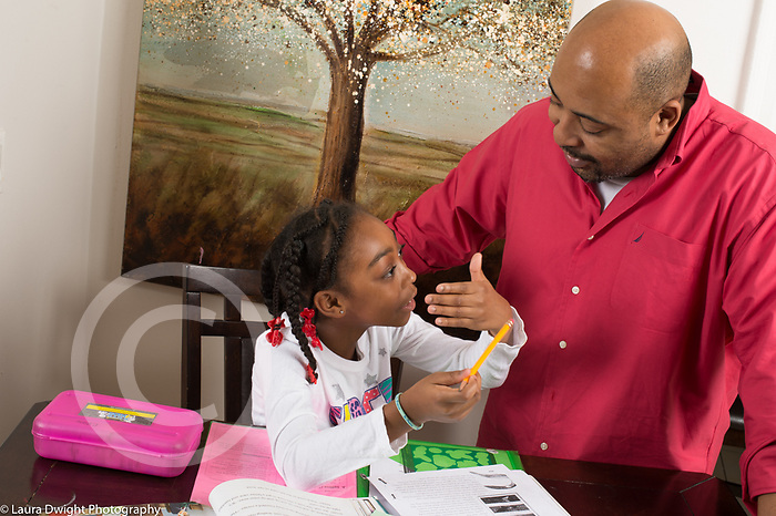 8 year old girl doing homework with father's assistance, talking to him, gesturing