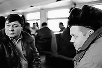"""Ukraine. Province of Kiev. Chernobyl. Two firemen are going back home after their two weeks shifts at Chernobyl. Winter season. The train """"Elektrichka"""" connects Chernobyl atomic power station to the town of Slavutich. It carries the workers inside the 30 km exclusion zone. The dead zone has been created after the catastrophe which took place on april 1986 at 1.23 am with the explosion of reactor No 4 at Chernobyl atomic power station. © 2006 Didier Ruef"""