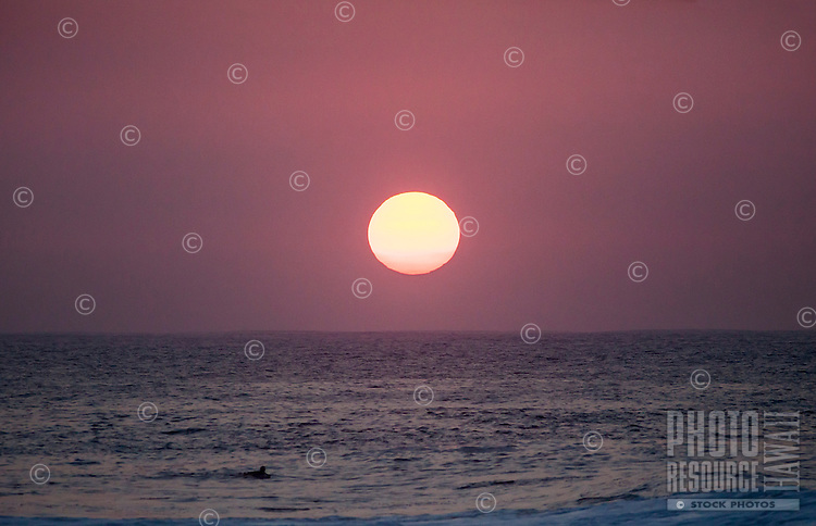 A close-up of a voggy sunset behind a surfer paddling at Rock Piles beach on the North Shore, O'ahu