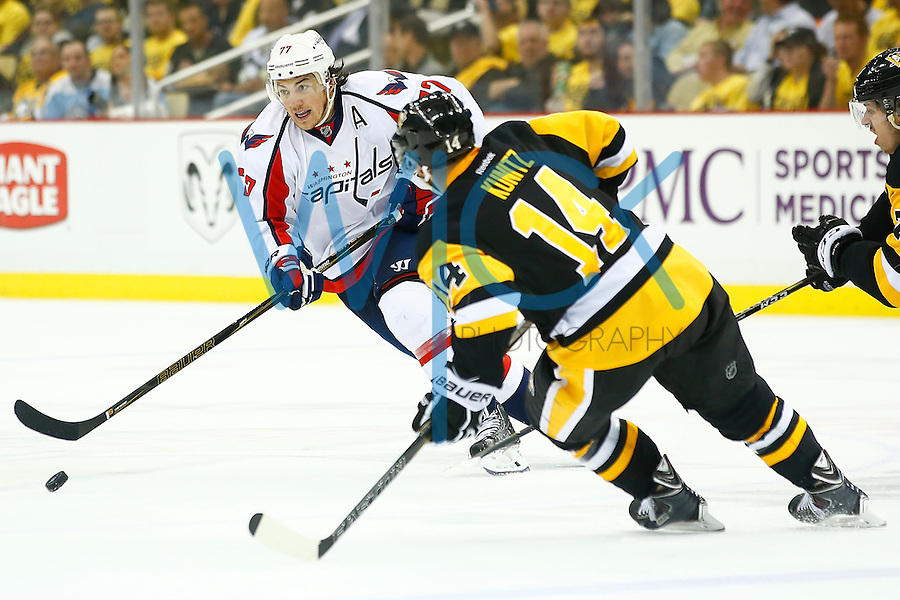 T.J. Oshie #77 of the Washington Capitals skates with the puck in front of Chris Kunitz #14 of the Pittsburgh Penguins in the third period during game three of the second round of the Stanley Cup Playoffs at Consol Energy Center in Pittsburgh, Pennsylvania on May 2, 2016. (Photo by Jared Wickerham / DKPS)