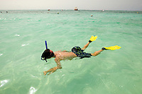 A young boy swims in the aqua Caribbean water on a beach slightly south of Cancun, Mexico.