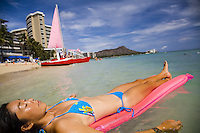 Asian woman sunbathing on a pink float in Waikiki Beach, with Diamond Head in the background