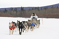 Jason Mackey sits on his seat as his teams glides down the Kuskokwim river shortly before McGrath on Wednesday during Iditarod 2008