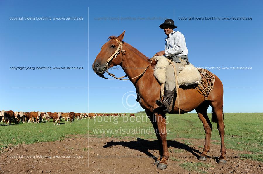 URUGUAY Estancia La Magdalena bei Salto, 18.ooo Hektar Weideland fuer 12.000 Rinder und 18.000 Schafe und 5.000 hektar Ackerland fuer Reis, Gensoja und Zuckerhirse, Gauchos auf Pferd treiben eine Rinderherde /.URUGUAY Salto, ranch La Magdalena, a gaucho ( cowboy ) on horse and cows