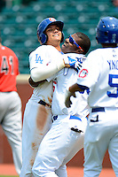 Chattanooga Lookouts outfielder Yasiel Puig #66 hugs teammate Miguel Rojas #13 after Rojas game winning hit during a game against the Birmingham Barons on April 17, 2013 at AT&T Field in Chattanooga, Tennessee.  Chattanooga defeated Birmingham 5-4.  (Mike Janes/Four Seam Images)