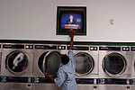 BROOKLYN  --  SEPTEMBER 30, 2004:  A man turns up the volume on the television, airing a live broadcast of a 2004 Presidential Debate between President George W. Bush and Senator John Kerry, in a Brooklyn Laundromat on September 30th, 2004 in New York City.  (PHOTOGRAPH  BY MICHAEL NAGLE)