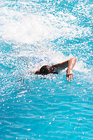A young teenage man boy crawling swimming in a bright blue swimming pool Clos des Iles Le Brusc Six Fours Cote d'Azur Var France