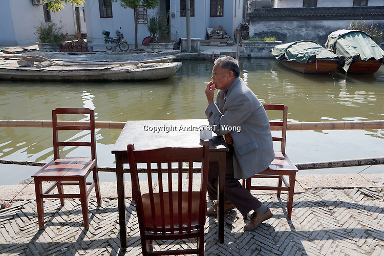 A villager smokes a cigarette along a canal in Zhouzhuang Town of Jiangsu Province, China on November 18, 2008. Zhouzhuang, one of the most famous water townships in China, is noted for its profound cultural background, the well preserved ancient residential houses, the elegant watery views and the colourful local traditions and folklore. Sixty percent of the Zhouzhuang's structures were built during the Ming and Qing Dynasties from 1368 to 1911.