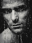 Man face wet from water pouring on it, artistic dramatic black and white portrait. Image © MaximImages, License at https://www.maximimages.com