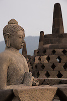 Borobudur, Java, Indonesia.  Statue of the Buddha near the Top of the Temple.  The diamond-shaped holes in the stupa in the background symbolize the passions that still linger as men rise toward Nirvana.