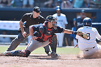 Rome Braves catcher Tanner Murphy (14) fields the ball and tags out Luis Jean (3) as home plate umpire Kyle Wallace watches during a game against the Asheville Tourists on July 26, 2015 in Asheville, North Carolina. The Tourists defeated the Braves 16-4. (Tony Farlow/Four Seam Images)