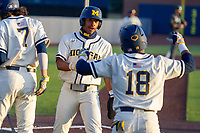 Michigan Wolverines Clark Elliott (15) celebrates with Jordon Rogers (18) after scoring in the ninth against the Michigan State Spartans on March 21, 2021 in NCAA baseball action at Ray Fisher Stadium in Ann Arbor, Michigan. Michigan scored 8 runs in the bottom of the ninth inning to defeat the Spartans 8-7. (Andrew Woolley/Four Seam Images)