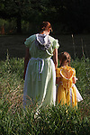 A mohter and daughter walking together in prairie dresses outside