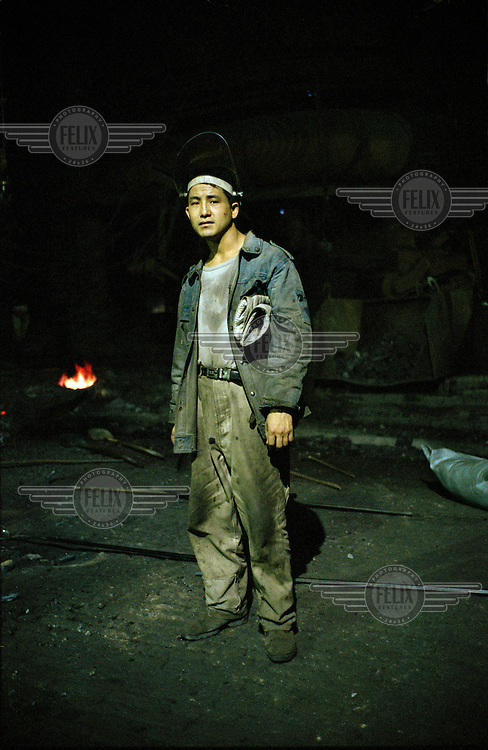 A portrait of a 22-year-old industrial steel worker. His wage is around 1000 RMB per month.
