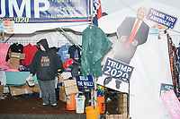 Rachel Bamber arranges Trump memorabilia and souvenirs for sale in a vendor's tent on the day of New Hampshire Presidential Primary voting in Manchester, New Hampshire, on Tue., Feb. 11, 2020.