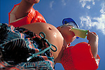 worm's-eye view of young boy in bathing suit eating popsicle