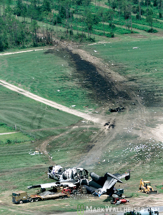 """The burned out remains of a Fed Ex 727 that crashed just before 6 am this morning, Friday July 26, 2002, at the Tallahassee airport.  The jet left a swath of black, clipping trees on it's path down before landing near construction equipment at the intersection of the airport's two main runways.  When firecrews arrived, they found the three crew members """"standing there in the smoke,"""" said one firefighter.  The airport fire rescue had been alerted by the control tower by an employee that arrived prior to his shift and the opening of the control tower.  The plane was already down.     (Mark Wallheiser/TallahasseeStock.com)"""
