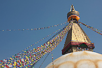 Bodhnath, Nepal.  The All-Seeing Eyes of the Buddha Gaze out from above the Stupa of Bodhnath, a center of Tibetan Buddhism, near Kathmandu.  The 13 tapering levels above the dome represent the 13 stages of perfection leading to nirvana.