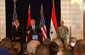 Zalmay Khalilzad, left, United States Ambassador to Iraq, and General George Casey, right, commanding general, Multinational Forces-Iraq, listen as United States President George W. Bush commends U.S. and coalition forces for their continuing efforts in Iraq June 13, 2006, at a former presidential palace of Saddam Hussein in Baghdad's International Zone. <br /> Credit: U.S. Navy via CNP
