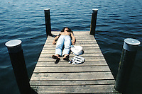 Switzerland. Zoug.  A young man sleeps on a wooden pontoon under the sun on the lake of Zoug . © 1989 Didier Ruef