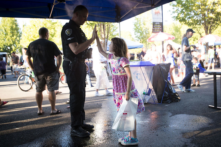 Beaverton City Police Department Officer Jeremy Shaw high-fives Isabelle Riley,7, under the misting station during National Night Out at Beaverton City Park.<br /> Photo by Jaime Valdez