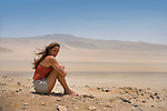 A Peruvian woman enjoys her time alone in the wind on the beaches of Reserva Nacional de Paracas, Peru.