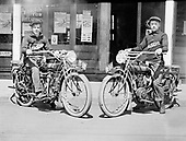 0405-C02. Two young men in front of the Newberg Cyclery, a motorcycle and bicycle store in Newberg, Oregon, located at 721 First St. East, owned by Harry Garrett. 1914 license plate. Indian motorcycle.