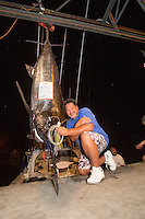 Bomboy Llanes, captain of the fishing boat Lana Kila, poses with a Pacific blue marlin grander at Honokohau Harbor, Big Island; he holds the Bomboy Lure that was used to catch the 1,041-lb. fish.