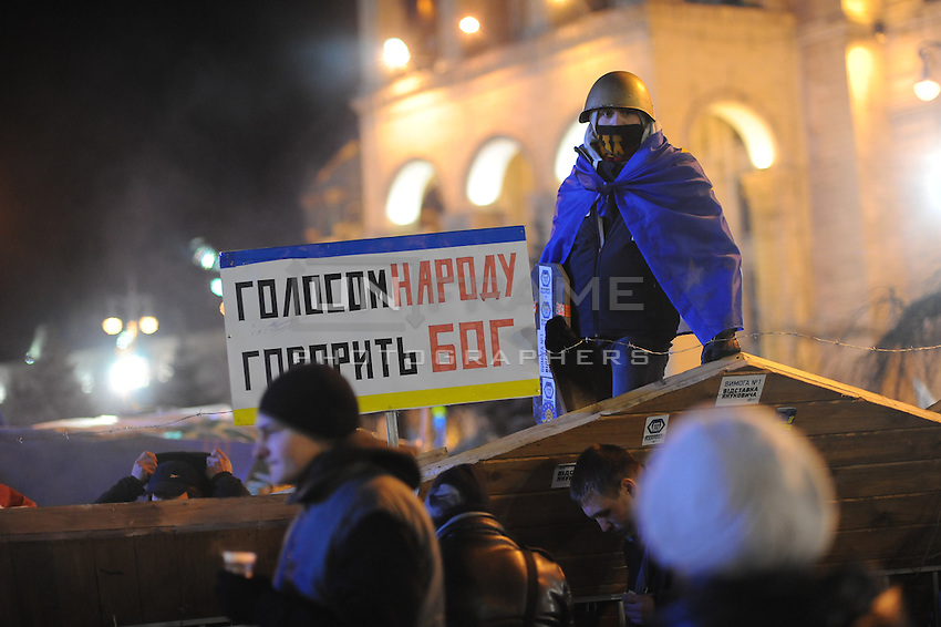 """Barricades built around Independence square in Kiev. """"God speaks through nation"""" sign says."""