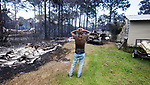 Faron Bryant looks over his property after wildfires swept through his neighborhood on Ridge Rd in Eastpoint, Fla., Monday, June 25, 2018. Bryant's home only lost it's siding but his workshop with his tools, a truck and boat, left, were destroyed. His neighbor's house at left was completely destroyed (AP Photo/Mark Wallheiser)