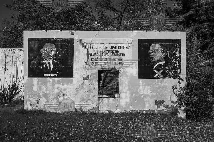 Murals of Martin Luther King and Malcolm X on the wall of a disused building.