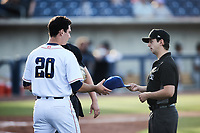 Kannapolis Cannon Ballers starting pitcher Andrew Dalquist (20) has his cap handed back to him by umpire Ethan Gorsak after having it inspected for foreign substances during the game against the Fayetteville Woodpeckers at Atrium Health Ballpark on June 22, 2021 in Kannapolis, North Carolina. (Brian Westerholt/Four Seam Images)