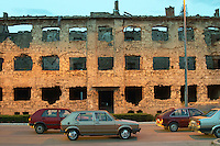 Building in Mostar damaged by the war and still not renovated. Ruined by bullet holes, mortar bomb shell grenade damage, very close to the beautifully renovated old town city centre. Along a busy main street in evening light with yellow street light giving an eerie atmosphere. Modern cars on the street. Town of Mostar. Federation Bosne i Hercegovine. Bosnia Herzegovina, Europe.