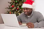 USA, Illinois, Metamora,  Man in Santa hat using laptop