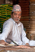 Kathmandu, Nepal.  Market Vendor Wearing a Topi, a Traditional Nepali Hat.  He has the remnant of a bindi on his forehead, a red mark worn as a blessing.