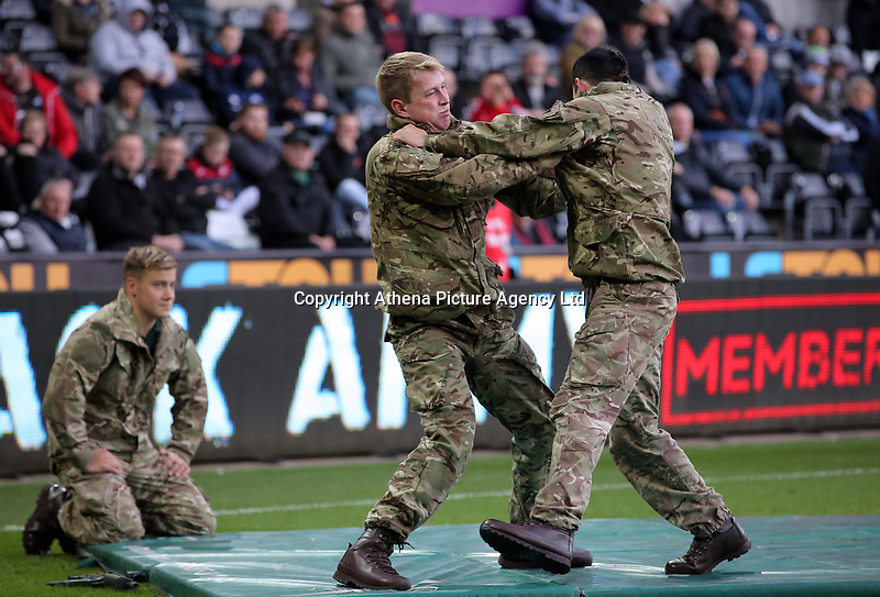 Members of the armed forces entertain the crowds during the Premier League match between Swansea City and Brighton and Hove Albion at The Liberty Stadium, Swansea, Wales, UK. Saturday 04 November 2017