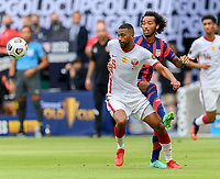 AUSTIN, TX - JULY 29: Gianluca Busio #6 of the United States and Abdelaziz Hatim #6 of Qatar chase after a loose ball during a game between Qatar and USMNT at Q2 Stadium on July 29, 2021 in Austin, Texas.