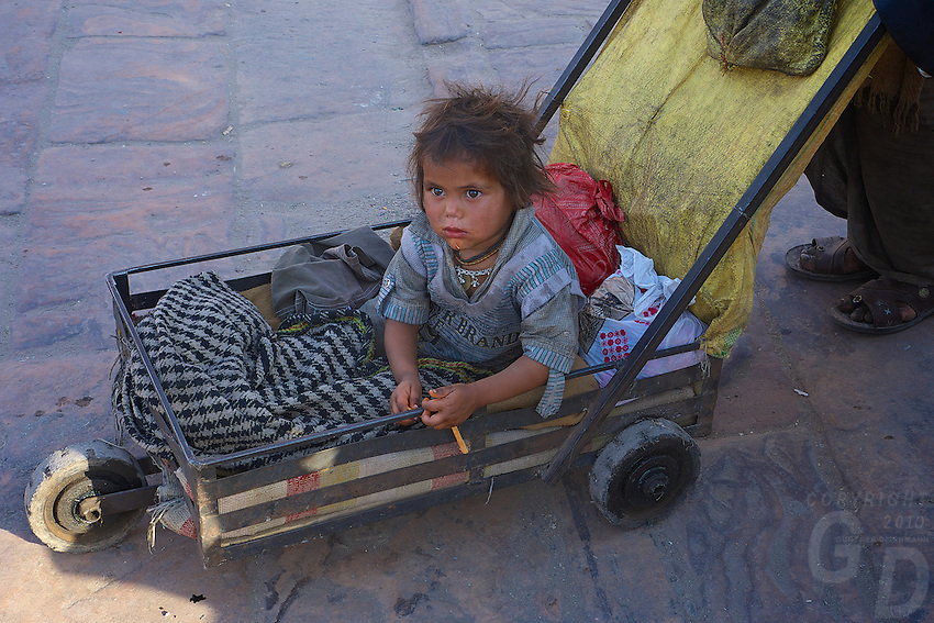 """Poverty, a child is been pushed around in a very primitive cart. Jodhpur Rajasthan India. The city is known as the """"Sun City"""" for the bright, sunny weather it enjoys all the year round. It is also referred to as the """"Blue City"""" due to the vivid blue-painted houses around the Mehrangarh Fort. The old city circles the fort and is bounded by a wall with several gates."""
