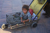 "Poverty, a child is been pushed around in a very primitive cart. Jodhpur Rajasthan India. The city is known as the ""Sun City"" for the bright, sunny weather it enjoys all the year round. It is also referred to as the ""Blue City"" due to the vivid blue-painted houses around the Mehrangarh Fort. The old city circles the fort and is bounded by a wall with several gates."