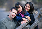 A family of three posing for an outdoor portrait along a wooden fence near Lumpy Ridge, Rocky Mtns, CO