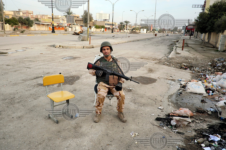 Omar, a soldier from 75th brigade of 16th division guards an entrance to the street where his brigade is based.