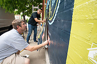 Robbie Hanner of Bentonville (left) and Jose Hernandez of Bella Vista apply a heat seal vinyl sign Monday May 3, 2021 to a brick wall of the Experience Fayetteville office on Fayetteville. The men work for Amp Sign and Banner. The sign commemorates the Square to Square Bike Ride between the Fayetteville and Bentonville squares that was held last Saturday. Visit nwaonline.com/210503Daily/ and nwadg.com/photo. (NWA Democrat-Gazette/J.T. Wampler)
