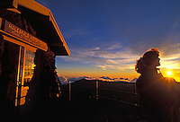A woman silhouetted by the rising sun stands next to the visitor center at a 9,745-ft. elevation in Haleakala National Park.