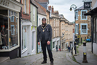 BNPS.co.uk (01202) 558833<br /> Pic: ZacharyCulpin/BNPS<br /> <br /> Pictured: Mayor Andy in Frome town centre<br /> <br /> At 6ft 9in tall, dressed all in black, with a big beard and wearing wayfarer shades, Andy Wrintmore does not look like your typical mayor.<br /> <br /> But the 29-year-old hardcore punk rock drummer is a big hit with old and young constituents in his hometown of Frome, Somerset.<br /> <br /> Andy, a member of punk band SickOnes, was elected to the town council by a landslide vote in 2019 and chosen to become the town's mayor in May this year.<br /> <br /> He has earned the moniker the 'punk rock mayor of Frome' and has even been interviewed by Kerrang magazine about his new career - cutting ribbons and meeting local community groups.
