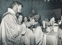 """Rev. Daniel Heap administers communion to young worshipper during service at Holy Trinity Church. Readers below criticize attack on St. John's (Norway) Anglican Church for allowing the very young to receive communion. """"Children should feel part of church,"""" they say."""