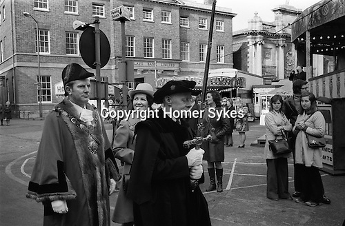 THE KINGS LYNN MART NORFOLK. Mart Fair. Kings Lynn, Norfolk 1974. 14 February, the Mayor Mr Edgar E.G. Edgley and Lady Mayoress process to the opening of the Charter Fair granted by Henry VIII in 1537, and as such is considered one of the oldest Mart fairs in the world.<br /> <br /> The first recorded Charter granted to the town was in 1204. However the Charter marking the Valentine's Day fair was granted by Henry VIII in 1537.<br /> <br /> The first recorded Charter granted to the town was in 1204 during the reign of King John. A Charter marking the Valentine's Day fair was granted by Henry VIII in 1537, and as such is considered one of the oldest Mart fairs in the world.  The fair takes place in the Tuesday Market Place with the Mayor and Chairman of the Markets Committee accompanied by local dignitaries and officials of the Showmen's Guild performing an opening ceremony by a blessing on the fair and the show people who attend it. This Valentine's Day fair is traditionally the first showman's fair of the year.<br /> During the later half of the nineteenth century the Mart was a spectacular event in which Frederick Savage of King's Lynn displayed his latest roundabouts and fairground attractions to the showmen. This display of new machines and amusements continues with the showmen vying to display the latest amusements. In 1897 Randall Williams became the first showman to display moving pictures at the fair. By the following year four cinematograph booths were on display.<br /> After the opening ceremony it is now traditional for local dignitaries to take rides on various fair ground attractions.<br /> <br /> My ref 6a/715/1974